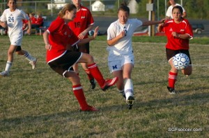 Kelly Smith, West Plains clears ball in front of Jennifer McArthur, Marshfield